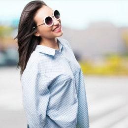 Perempuan muda yang tampak bahagia mengenakan kacamata putih, rambutnya yang panjang tertiup angin.