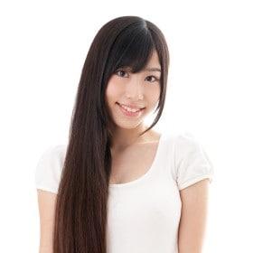Perempuan berambut panjang dan hitam, dengan rambut diikat ekor kuda tersenyum ke arah kamera.