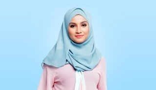 Perempuan menggunakan hijab warna biru muda tersenyum ke arah kamera.