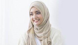 Perempuan tersenyum mengenakan hijab yang berkilau emas.