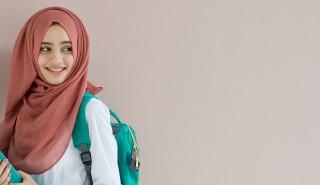 Perempuan muda yang tampak bahagia, mengenakan hijab merah muda dan tas sekolah warna biru.