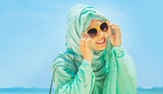 Perempuan memakai hijab untuk musim panas dan kacamata berwarna kuning cerah.